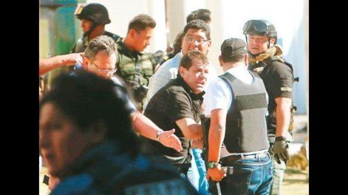 El gerente Peña, al momento de ser evacuado del lugar del tiroteo por policías en un vehículo. Foto: El Deber